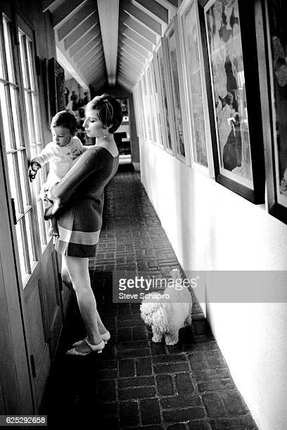 American actress and musician Barbra Streisand holds her son Jason in a hallway in their home Beverly Hills California 1967