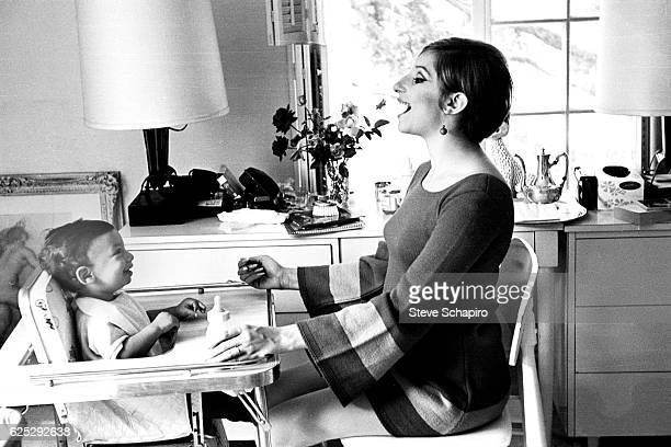 American actress and musician Barbra Streisand makes a face as she feeds her son Jason in their home Beverly Hills California 1967