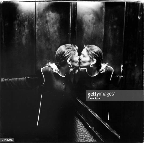 American actress and novelist Carrie Fisher plants a kiss on her reflection in the mirrored wall of a lift 18th April 1994