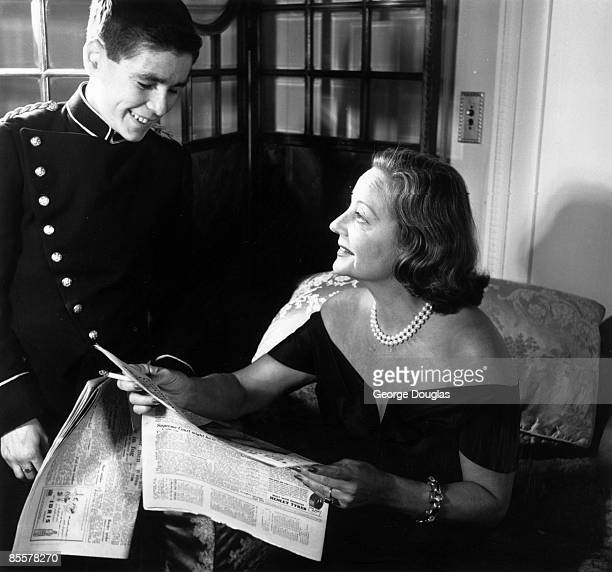 American actress and radio chatshow host Tallulah Bankhead chats with a bellhop at the Ritz Hotel during a visit to London September 1951 Original...