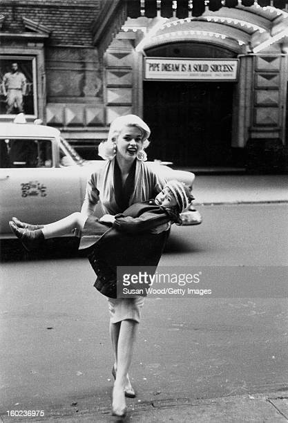 American actress and sex symbol Jayne Mansfield carries her daughter future actress and model Jayne Marie Mansfield across West 44th street in front...