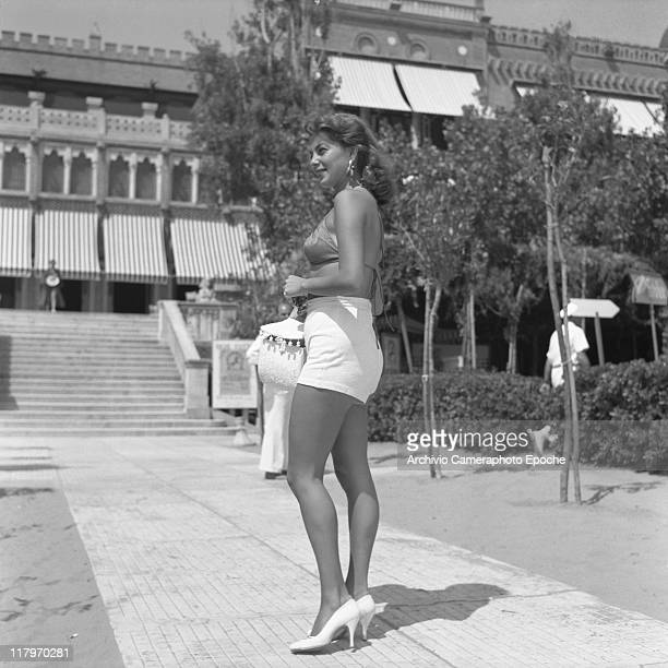 American actress and singer Abbe Lane, wearing a swimming bra and a high-waisted hot pants, holding a handbag, standing on the path of the Excelsior...