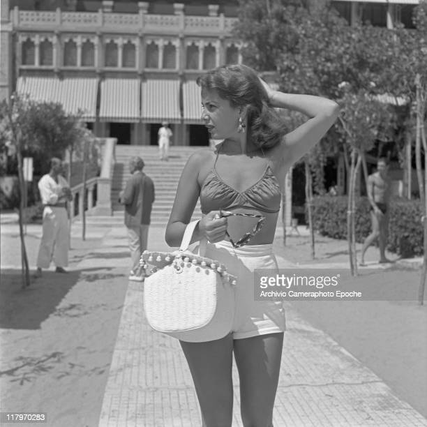 American actress and singer Abbe Lane, wearing a swimming bra and a high-waisted hot pants, holding a handbag and sunglesses, portrayed standing on...