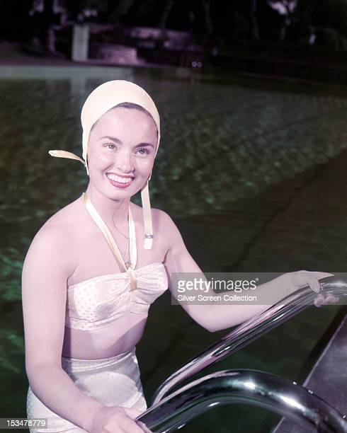 American actress and singer Ann Blyth emerging from a swimming pool in a bikini and swimming cap circa 1950
