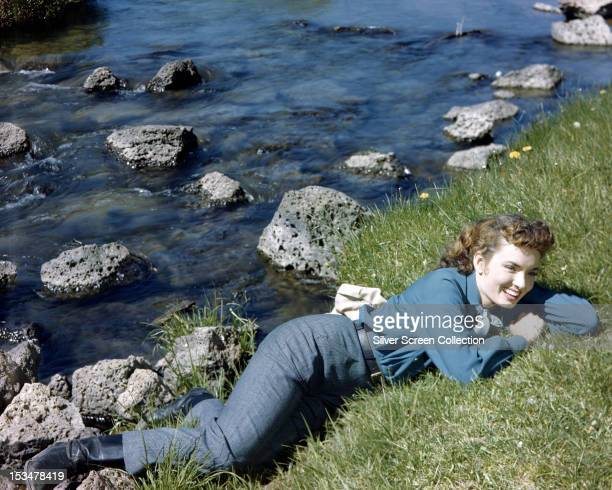 American actress and singer Ann Blyth lying by a rocky stream circa 1945