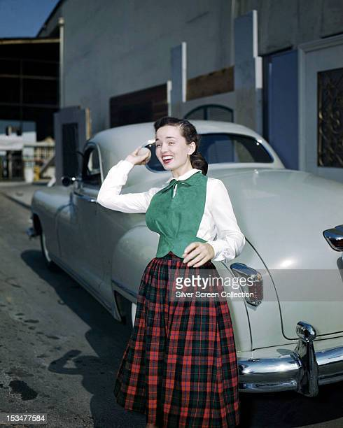 American actress and singer Ann Blyth throwing a ball circa 1940 She is standing next to a car and is wearing a plaid skirt