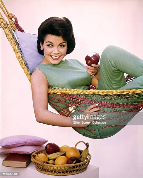 American actress and singer Annette Funicello lying in a hammock and eating an apple circa 1965