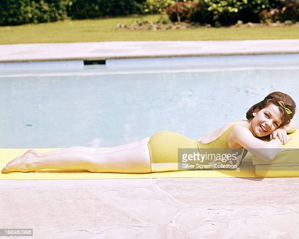 American actress and singer Annette Funicello lying next to a swimming pool in a onepiece swimsuit circa 1965