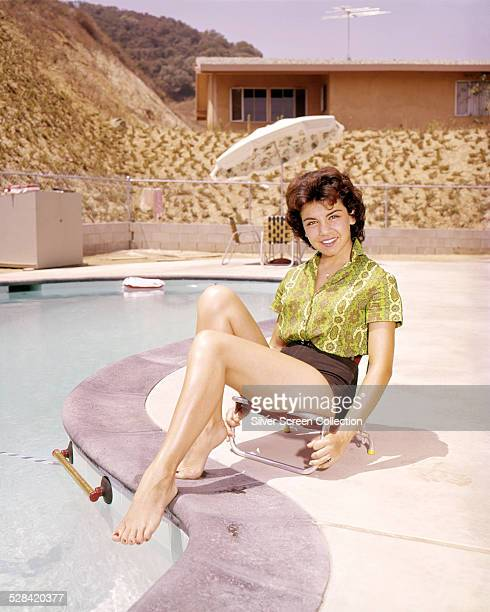 American actress and singer Annette Funicello sitting by a swimming pool circa 1960