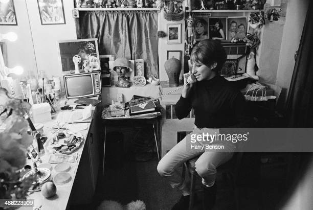 American actress and singer Barbra Streisand makes a phone call from her dressing room 6th October 1965 On the wall are portraits of her husband...