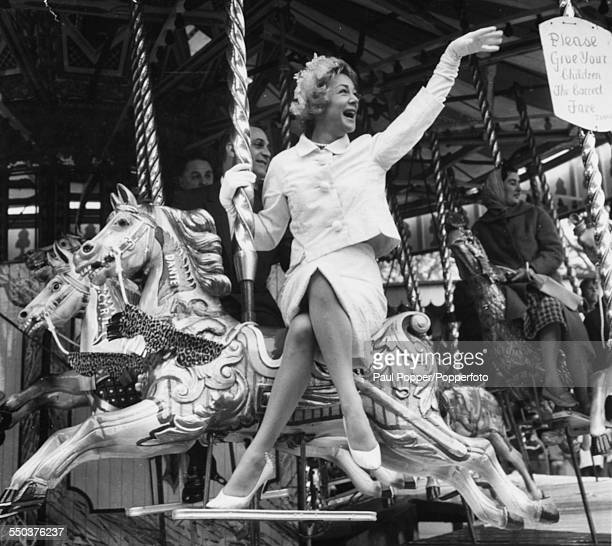American actress and singer, Betty Hutton smiling as she rides a carousel, at the season opening of the fun fair at Battersea Festival Gardens,...