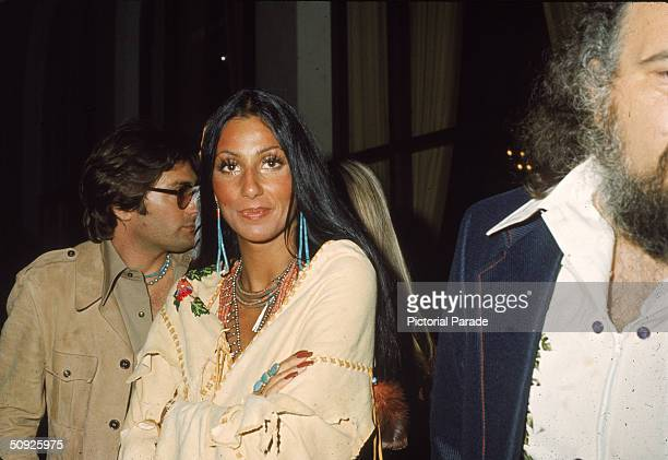 American actress and singer Cher wears beaded jewelry as she stands with arms crossed in a Native American poncho at the premiere of 'Last Tango in...