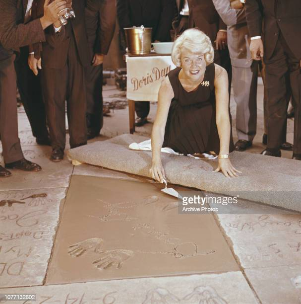 American actress and singer Doris Day plants her handprints in cement outside Grauman's Chinese Theatre, Hollywood, California, 19th January 1961.