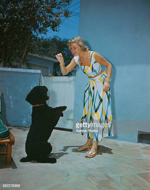 American actress and singer Doris Day playing with a dog circa 1950