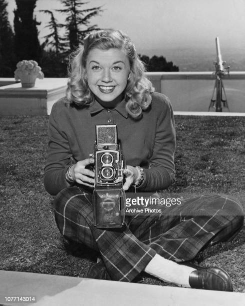 American actress and singer Doris Day using a camera, circa 1950.