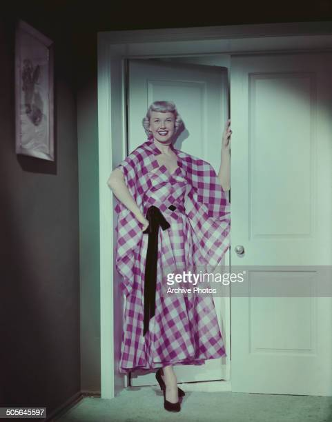 American actress and singer Doris Day wearing a pink and white checked evening dress circa 1955