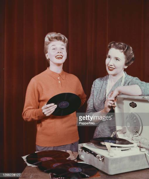 American actress and singer Doris Day wearing an orange long sleeved polo shirt holds a LP record as she listens to discs being played on a portable...