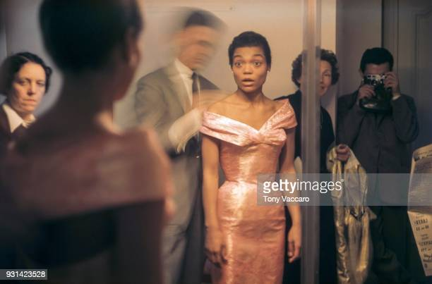 American actress and singer Eartha Kitt looks at her reflection in a fulllength mirror as French fashion designer Hubert de Givenchy adjusts her...