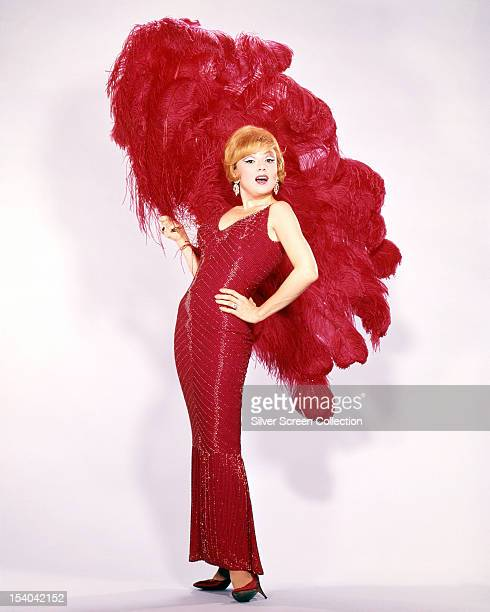 American actress and singer Edie Adams wearing a red sheath dress and holding red ostrich feathers circa 1965