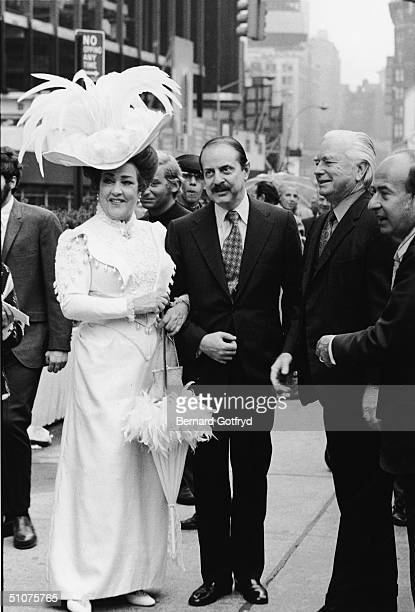 American actress and singer Ethel Merman dressed in am elaborate costume complete with a feathered hat and a parasol stands holding the arms of...