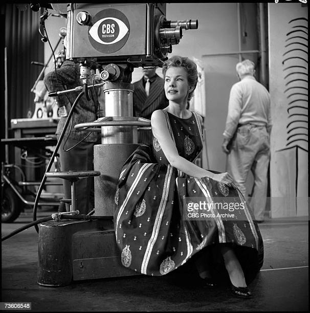 American actress and singer Gale Storm sits at the foot of a television camera during a break in the filming of the television program 'The Big...