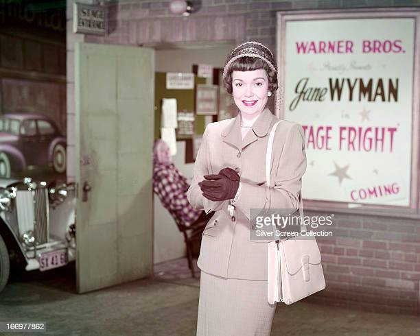 American actress and singer Jane Wyman standing next to a poster for her latest film Alfred Hitchcock's 'Stage Fright' 1950