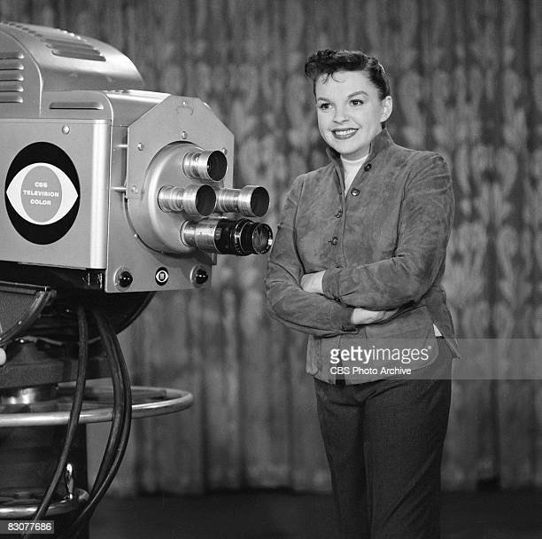 American actress and singer Judy Garland stands next to a television camera on the set of the live performance anthology series 'Ford Star Jubilee'...