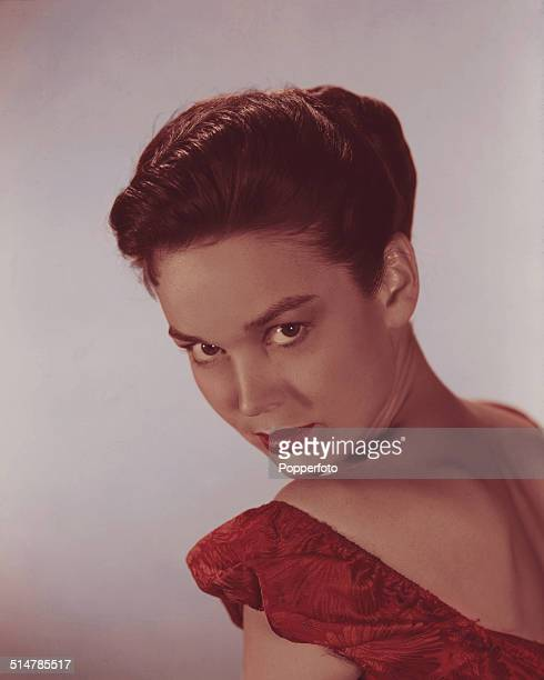American actress and singer Kathryn Crosby posed wearing a red off the shoulder dress circa 1955