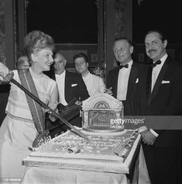 American actress and singer Mary Martin cuts her birthday cake a representation of a Drury Lane theatre at a party for the cast of the show 'Hello...