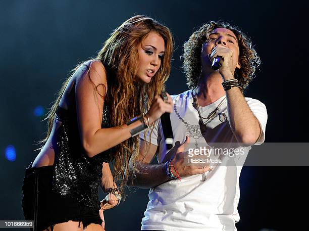 American actress and singer Miley Cyrus and Spanish pop singer David Bisbal perform on stage at the Rock in Rio Madrid music festival on June 6 2010...