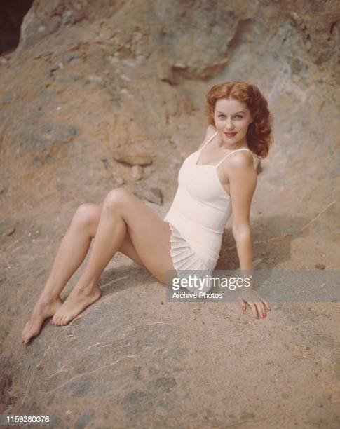 American actress and singer Rhonda Fleming in a white swimsuit with a pleated skirt circa 1955