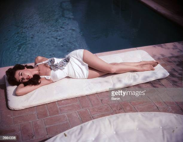 American actress and singer Rita Moreno lying by a pool, 1954. She the only woman to win show business' top four awards: Oscar, Grammy, Tony and Emmy.