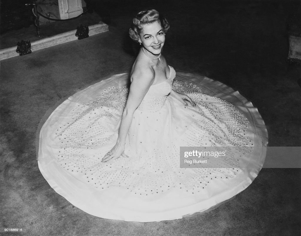 American actress and singer Vivian Blaine (1921 - 1995), star of the musical 'Guys and Dolls', tries on her dress for the Royal Command Performance at the London Coliseum, 30th October 1953. The dress is made of white georgette over white taffeta, decorated with pearl beads.