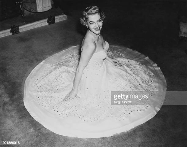 American actress and singer Vivian Blaine star of the musical 'Guys and Dolls' tries on her dress for the Royal Command Performance at the London...