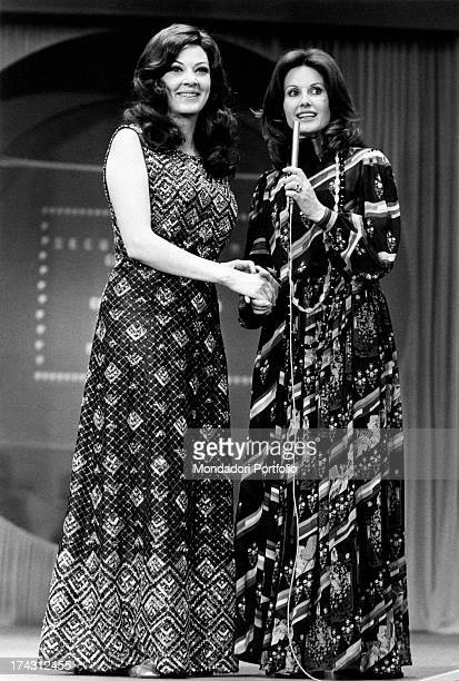 American actress and soprano Anna Moffo shaking hands with Italian television presenter and actress Gabriella Farinon on a stage 1973