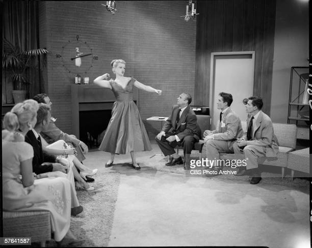 American actress Angela Lansbury stands and acts out charades on the 'Pantomime Quiz' game show featuring show regulars Jackie Coogan John Barrymore...