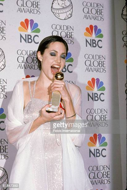 American actress Angelina Jolie licks her Golden Globe award for Best Performance by an Actress in a Supporting Role in a Series MiniSeries or Motion...