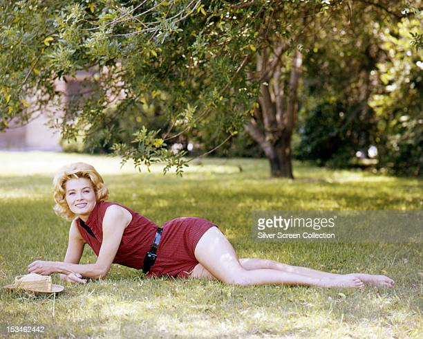 American actress Angie Dickinson in a red playsuit circa 1955