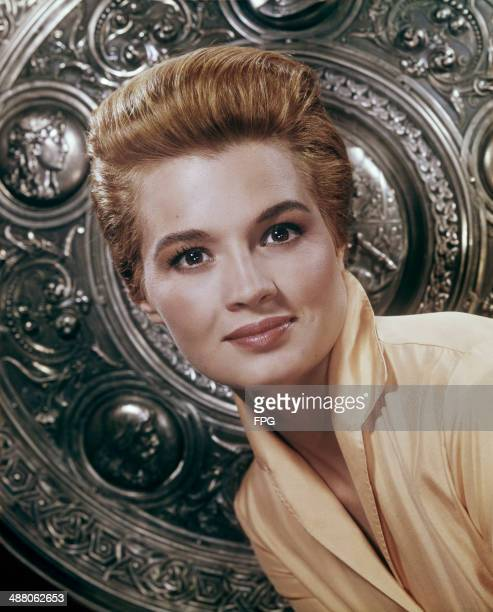 American actress Angie Dickinson in front of an embossed shield, circa 1960.
