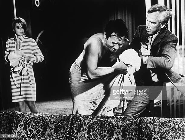 American actress Angie Dickinson looks on as Canadian actor John Vernon struggles with American actor Lee Marvin in a fight scene from the thriller...
