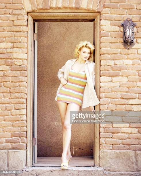 American actress Angie Dickinson standing in a doorway wearing a onepiece swimsuit under a jacket circa 1965