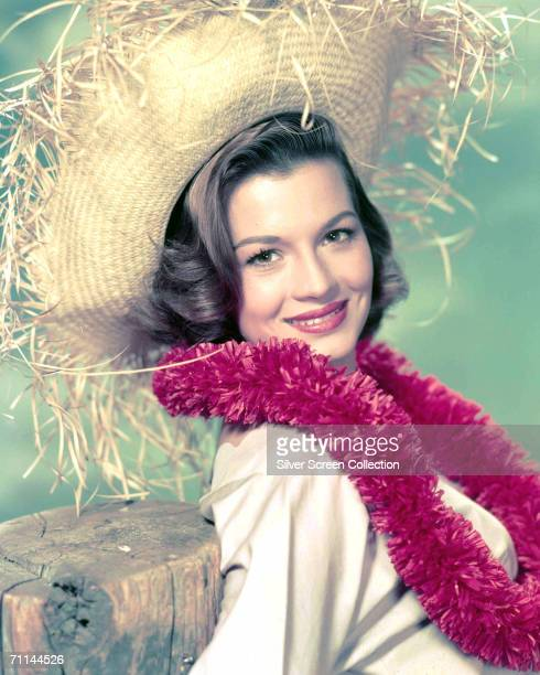 American actress Angie Dickinson wearing a pink garland and a straw hat, circa 1955.