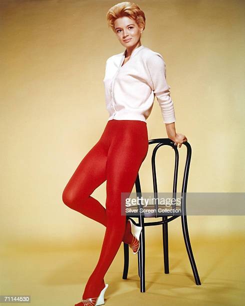 American actress Angie Dickinson wearing a white cardigan and red tights circa 1955