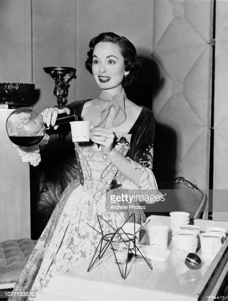 American actress Ann Blyth pours coffee on the set of the film 'The Student Prince' circa 1954