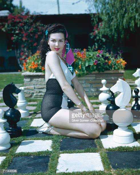 American actress Ann Miller kneeling on a giant outdoor chessboard circa 1955
