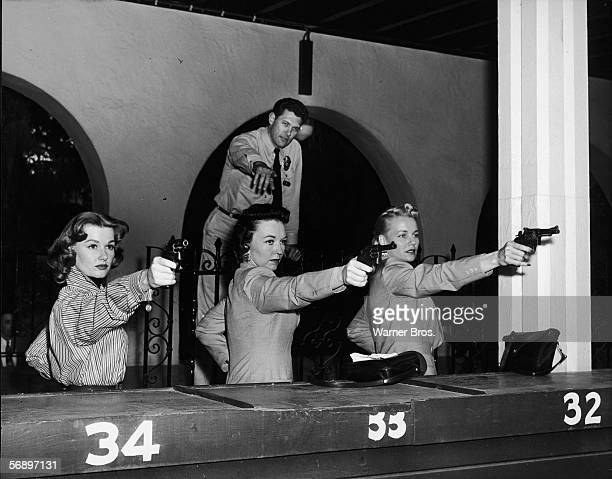 American actress Ann Robinson learns to shoot in the proper fashion from real policewomen Pat Wright and June Howard as shooting instructor Sergeant...