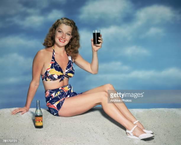 American actress Ann Sheridan enjoys a glass of Royal Crown Cola on the beach circa 1950