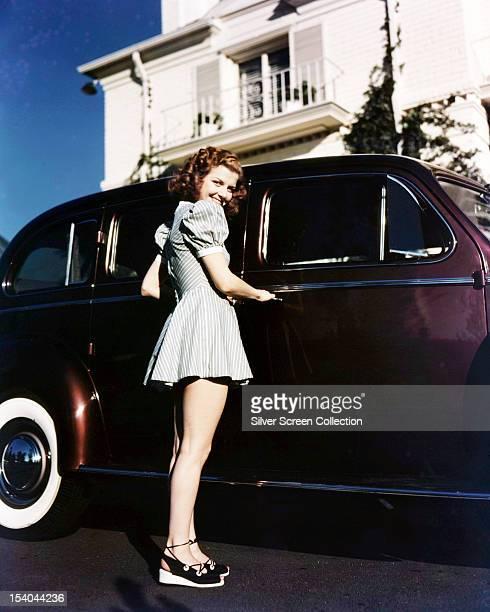 American actress Ann Sheridan wearing a short grey dress with puffed sleeves as she opens a car door circa 1945