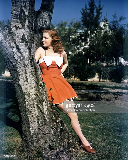 American actress Ann Sheridan wearing a short red dress decorated with a large white bow circa 1940