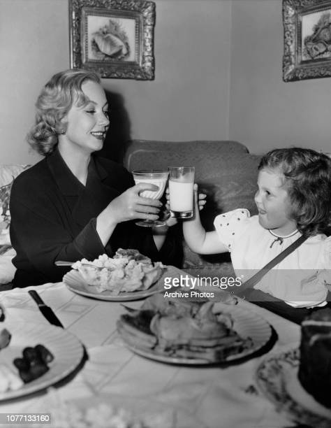 American actress Ann Sothern eats lunch with her daughter Tisha in her dressing room during filming of the MGM mystery thriller 'Death in the Doll's...